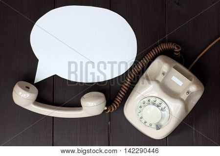 retro phone and the concept of the voice coming out of the tube lying on a wooden table top view / important telephone conversation