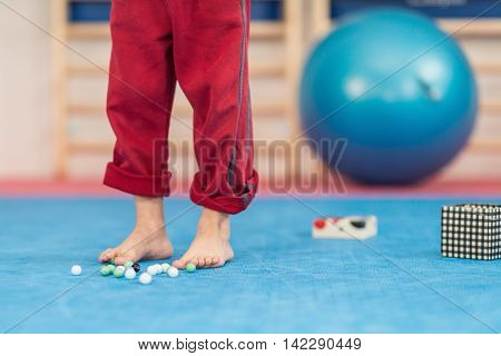Flat feet physical therapy - Little boy picking up marbles with his feet developing feet motor skills and flexibility
