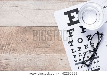 Healthy eyes. Eye chart and medicine on wood table