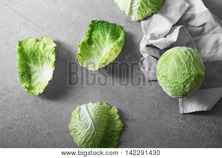 Fresh savoy cabbage and leaves on grey background, top view