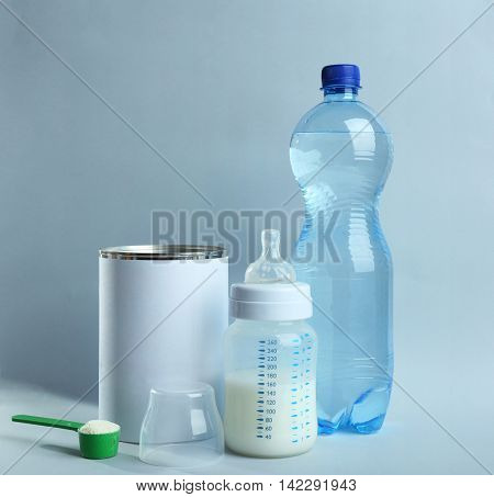 Baby milk formula and bottles on color background