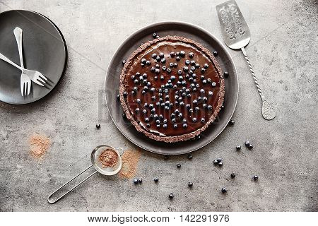 Delicious chocolate tart with blueberry on a color background