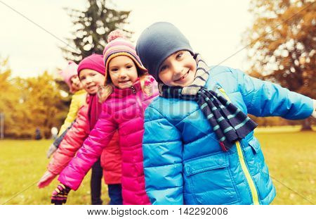 childhood, leisure, friendship and people concept - group of happy kids playing game and having fun in autumn park