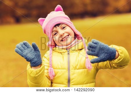 autumn, childhood, happiness and people concept - happy beautiful little girl waving hands outdoors