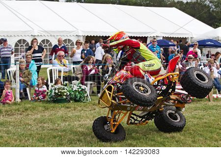 WEEDON, UK - AUGUST 28: An unnamed rider of the Kangaroo Kid quad stunt duo demonstrates how to ride an ATV on two wheels to the public at the Bucks County show on August 28, 2014 in Weedon.