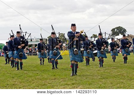 WEEDON, UK - AUGUST 28: Members of a local Pipe and Drum band perform Highland and military tunes for the public in the main show arena at the Bucks County show on August 28, 2014 in Weedon.