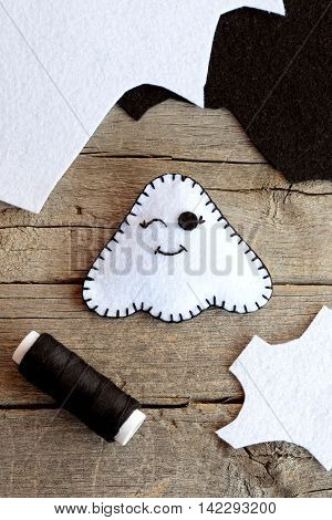 Cute Halloween ghost decor, felt sheets, black thread on an old wooden table. White ghost ornament made at home. Halloween children art diy. Sewing toy. Top view