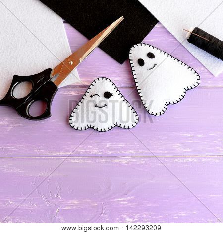 Two small Halloween ghosts diy, white and black felt sheets, scissors, thread, needle on lilac wooden background. Home Halloween decor project for kids. Sewing craft inspiration