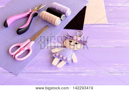 Adorable doll keychain, pliers, thread, needle, pins, scissors, felt, cord, hollofayber on wooden background with empty space for text. Supplies for sewing cute character. Crafts for children