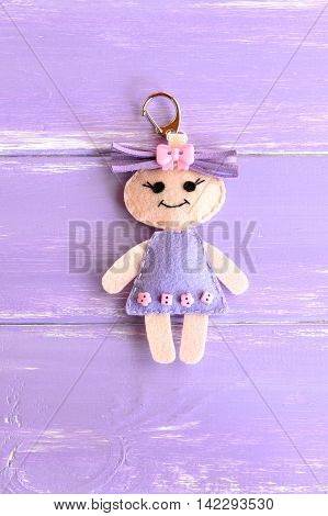 Cute little doll isolated on purple wooden background. Charm keychain for a children bag or backpack. Kids sewing crafts idea