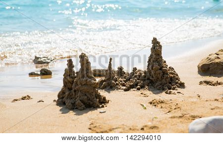 Sandcastle on beach against of sun reflection at the sea, Holiday concept image