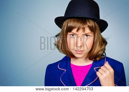 Stylish teen girl in a bowler hat. Children's fashion. Copy space.
