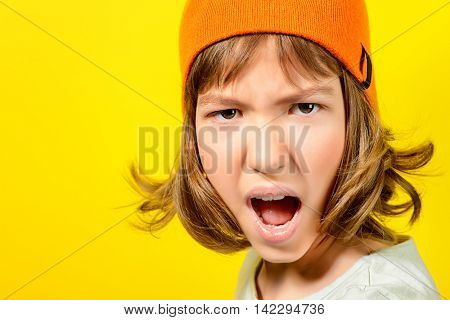 Portrait of a shouting angry teen girl over yellow background. Modern generation. Copy space.