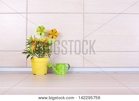 Pepper In Flower Pot And Watering Can On Kitchen Counter