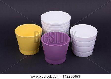 Empty flowerpots on dark background, studio shot
