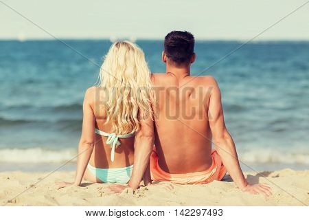 love, travel, tourism, summer and people concept - smiling couple on vacation in swimwear sitting on beach from back