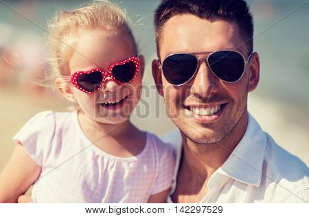 family, travel, vacation, adoption and people concept - happy father with little girl in sunglasses on summer beach