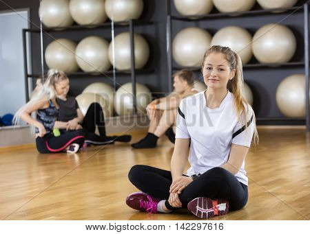 Smiling Woman Sitting Crossed Legged On Floor At Gym