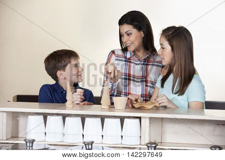 Family Choosing Between Cones And Cups At Counter