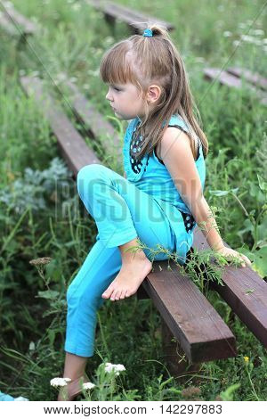 Little Girl With Long Hair Playing On Grass In Summer