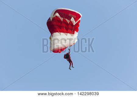 Parachutist with red parachute on a blue sky background.