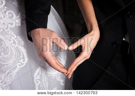 bride's and groom's hands in shape of heart on the background of the bride dress and groom's suit.
