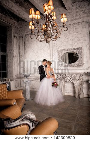 the bride and groom stand together in a luxurious gray interior. Expensive sofas around. Luxury chandelier on the ceiling.