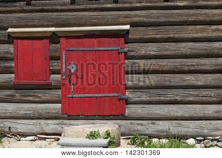 Red old door and window on the wooden wall of a village house. Excellent background