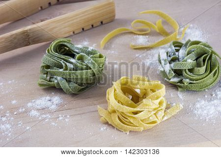 Three pieces of yellow and green pasta on wooden table