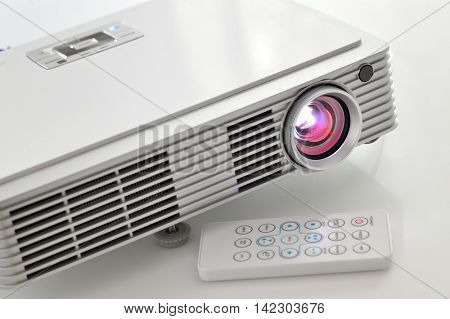 Portable led projector on white table