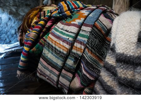 Multicolored blankets of wool drying after felting in a mountain river. Production of lizhnyk- a traditional craft in Carpathian villages. Traditional technology - weaving from hand spinning fleece