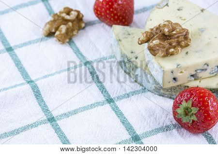 Two pieces of blue cheese roquefort with walnuts and strawberries on the towel