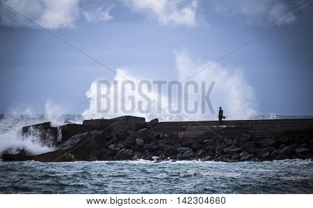 Stone Breakwater With Breaking Waves.