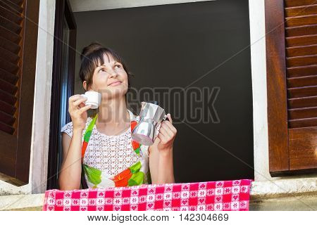 Portrait of middle-aged woman holding white cup of freshly brewed hot coffee and Italian moka pot sitting near open window with traditional European wood brown shutters.