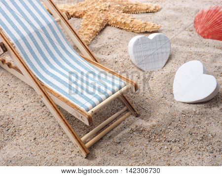 Blue deckchair with starfish in the sand on a beach