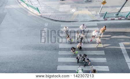Blur people are moving across the pedestrian crosswalk in the city road (on top view)