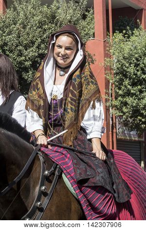 SELARGIUS, ITALY - September 14, 2014: Former marriage Selargino - Sardinia - portrait of a beautiful woman with a traditional Sardinian costumes parading with his horse - Sardinia