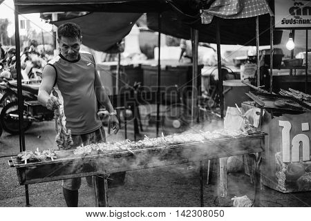 PrachuapkhirikhanThailand -January 24 2016: Unidentified man grilling chicken to sell in the thai traditional market Prachuapkhirikhan Province Thailand / high contrast black and white picture style