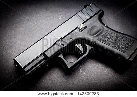 a polymer hand gun on black background,