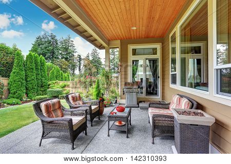 Cozy Covered Sitting Area With Wicker Chairs And Barbecue