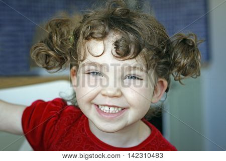 Portrait of cute preschool girl with hair tufts in kitchen smiling.