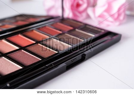 Eyeshadow makeup palette close up with roses on the background