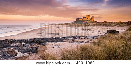 Golden Bamburgh Castle Panorama, on the Northumberland coastline, bathed in late afternoon golden sunlight