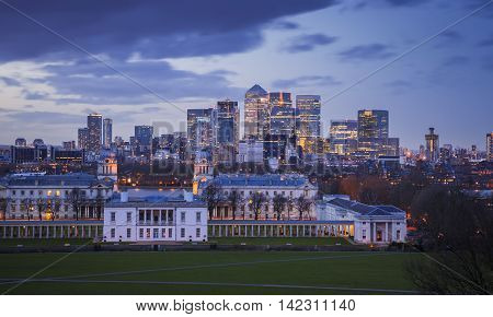 Skyline view of the skyscrapers of Canary Wharf and national maritime museum, shot from Greenwich park at blue hour - London, UK