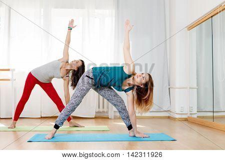 Two beautiful flexible women practices yoga asana extended triangle pose, utthita trikonasana