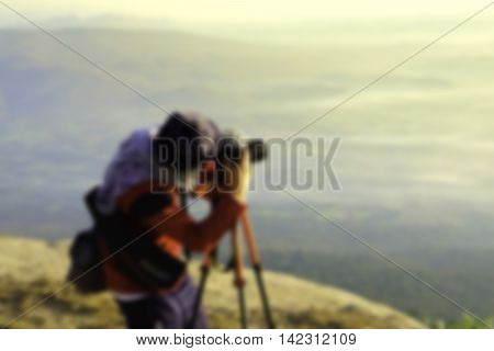 blurred image of hipster handsome man photography standing shooting camera with nature enjoy and happy at mountain.