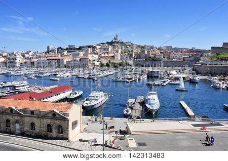 MARSEILLE, FRANCE - MAY 17: The Old Port on May 17, 2015 in Marseille, France, with the Notre-Dame de la Garde in the background. It is a busy port, used as a marina and terminal for boat trips
