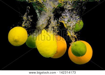 Citrus fruits fall into the water. Flying splashes and drops on a black background. Lime, lemon, orange.