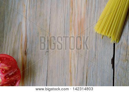 Raw Spaghetti Pasta And Half Tomato On Wood Background