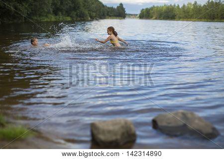 Two naughty girls bathe in the lake.